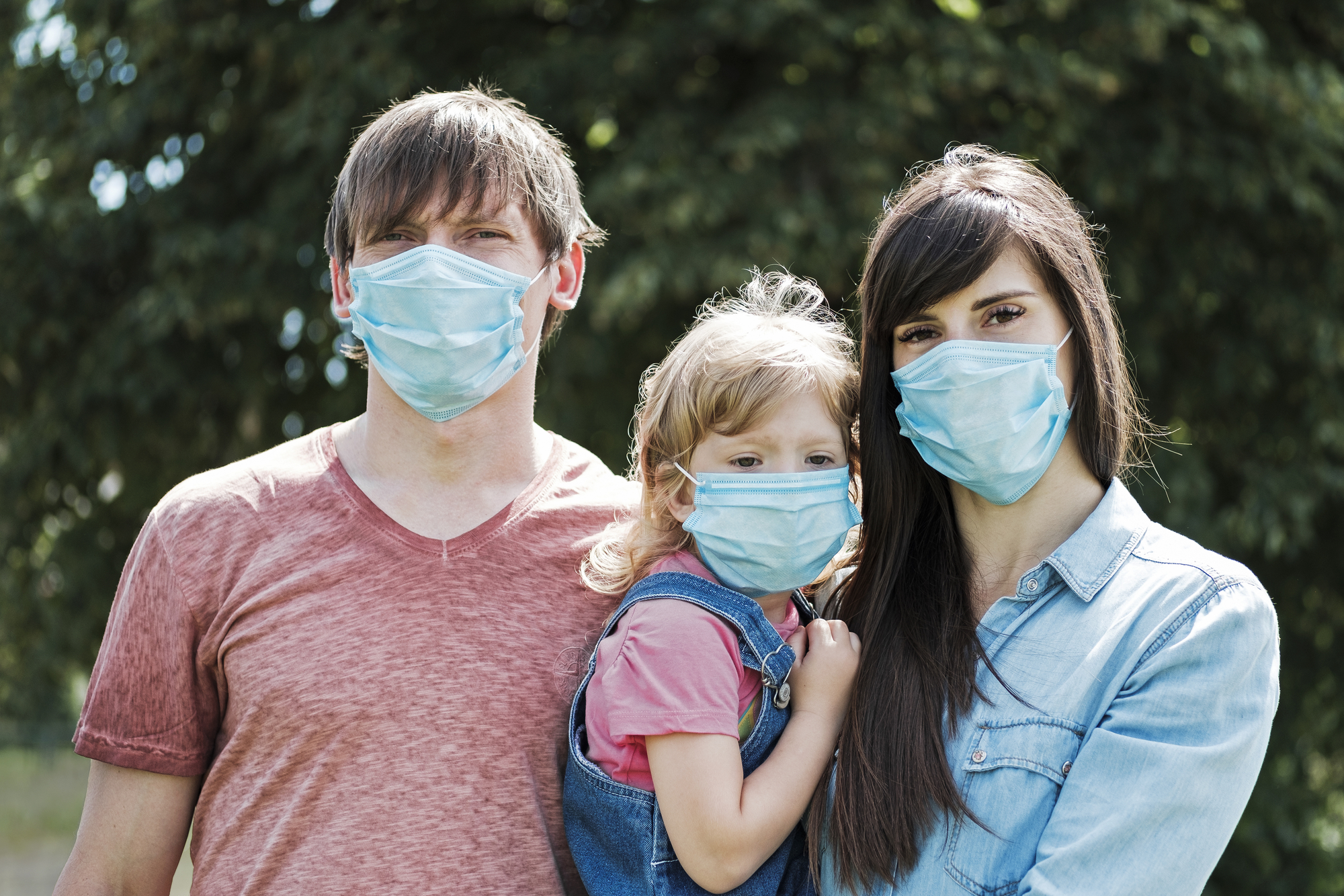 Young family with daughter wearing protective surgical face masks during the Covid-19 or coronavirus pandemic